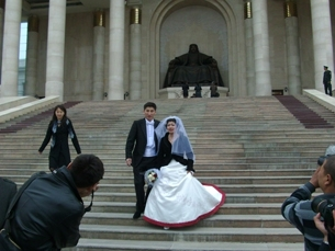 A newly married couple poses near a statue of Mongolia's national hero Genghis Khan.