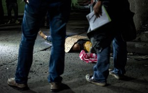 "Police officers investigate the body of an alleged drug dealer, his face covered with packing tape and a placard reading ""I'm a pusher,"" on a street in Manila, the Philippines, July 8, 2016."