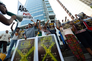Protesters holding mock covers of Chinese passports shout anti-Chinese slogans in front of the Chinese consular office in Manila Nov. 29, 2012.
