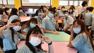 High school students from the San-Chung Commercial and Industrial Vocational High School, masked to prevent the spread of the coronavirus, pose for a photo before taking part in an English lesson at their school in New Taipei City, May 15, 2020.
