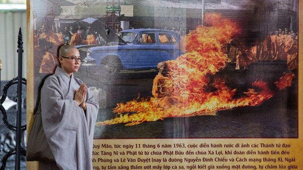 A Buddhist monk stands next to a banner with a picture of monk Thich Quang Duc, who set himself on fire on a busy Saigon street corner in 1963, at Quoc Tu pagoda in Ho Chi Minh City on the 55th anniversary of the self-immolation, June 3, 2018.