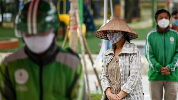 Residents wearing face masks practice social distancing as they wait in a queue for free rice, amid Vietnam's nationwide social isolation effort against the spread of the COVID-19 coronavirus, in Hanoi, April 11, 2020.