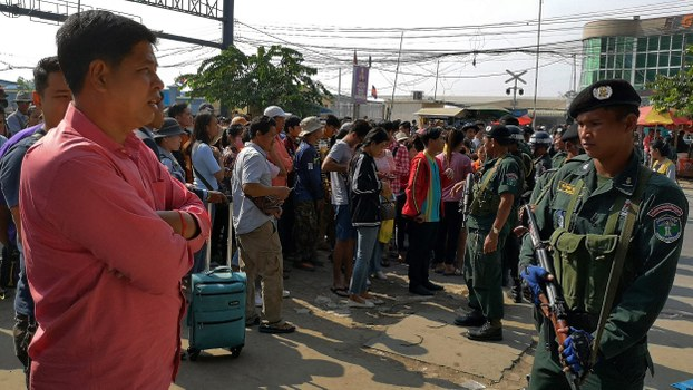Cambodian police (R) check people as they try to cross the border to Thailand in the Cambodian town of Poipet, Nov. 9, 2019.