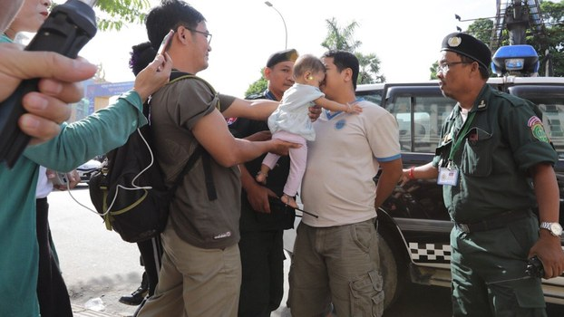CNRP activist Kong Raiya kisses his daughter as he is led to court for questioning in Phnom Penh, July 11, 2019.