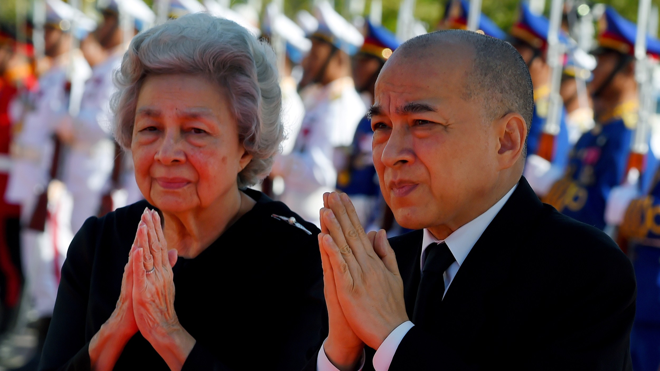 Cambodia's King Norodom Sihamoni (R) and his mother former queen Monique (L) walk past honor guards during the cremation of Princess Norodom Buppha Devi in front of a pagoda in Phnom Penh, Nov. 25, 2019.