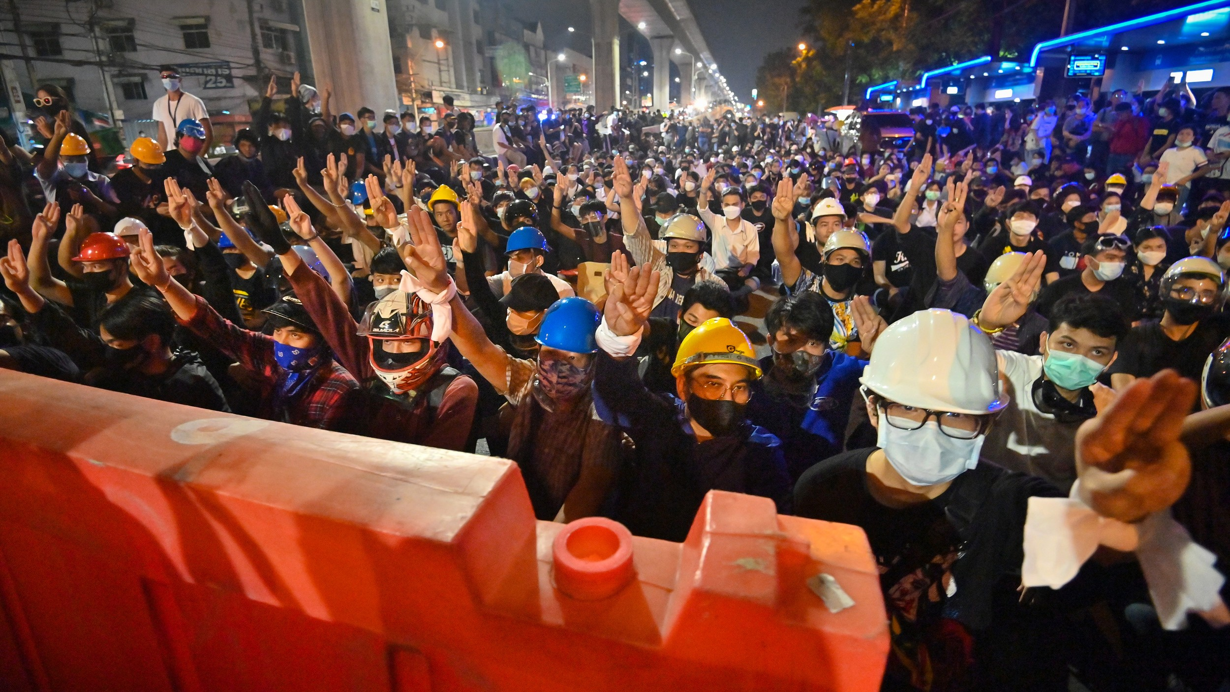 Pro-democracy protesters give the three-finger salute as they sit behind barricades during an anti-government rally at Kaset intersection in Bangkok, Oct. 19, 2020.