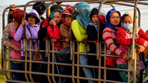 Garment factory workers stand in a truck they use to commute to and from work in Kampong Speu province, Dec. 12, 2019.