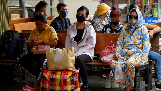 People wearing face masks as a preventive measure against COVID-19 sit at a bus station in Phnom Penh, March 18, 2020.
