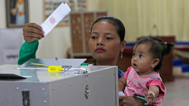 A woman holds a child as she casts a ballot in Cambodia's Kandal province, Feb. 25, 2018.