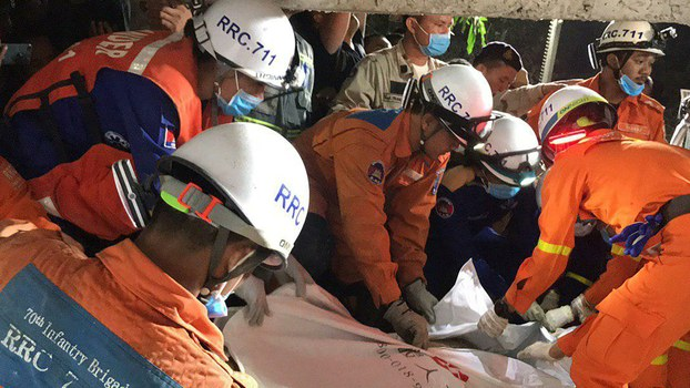 In this photo provided by the Kep Provincial Authority, emergency workers wrap the body of a victim of a building collapse in Kep province, southern Cambodia, Saturday, Jan. 4, 2020.