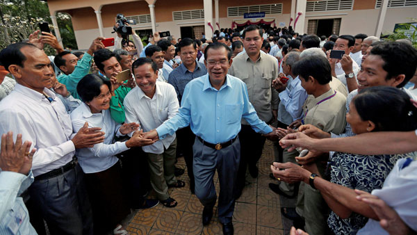 Cambodia's Prime Minister Hun Sen is surrounded by his commune counselors from his Cambodian People's Party during a Senate election in Takhmao, southeastern Cambodia's Kandal province, Feb. 25, 2018.