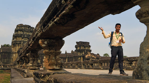 A Cambodian guide leads tourists during a visit to the Angkor Wat temple complex in northwestern Cambodia's Siem Reap province, March 5, 2020.