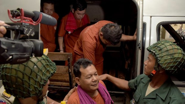 Suth Vanny (bottom C) Chay Sarith (top 2nd L) and Mao Hoeun (top L), three soldiers from Cambodian Prime Minister Hun Sen's elite bodyguard unit, are escorted by police at Phnom Penh's municipal court for sentencing in the 2015 brutal beating of  two opposition lawmakers, May 27, 2016.