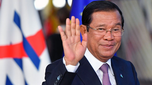 Cambodia's Prime Minister Hun Sen waves as he arrives for a Asia Europe Meeting (ASEM) at the European Council in Brussels, Oct. 18, 2018.