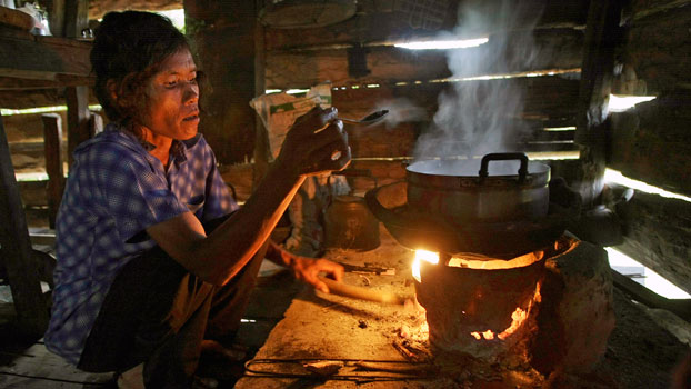 A Cambodian villager whose hut has no electricity cooks rice over a small wood-burning stove in Ta Thorng village, southwestern Cambodia's Koh Kong province, in a file photo.
