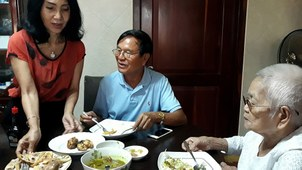 Cambodia opposition leader Kem Sokha (C) eats with his wife Te Chanmono (L) and mother Sao Nget (R) while confined by the government to his residence in Phnom Penh, September 11, 2018.