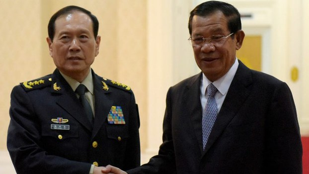 Cambodian Prime Minister Hun Sen (R) shakes hands with China's Defense Minister Wei Fenghe before their meeting at the Peace Palace in Phnom Penh, June 18, 2018.