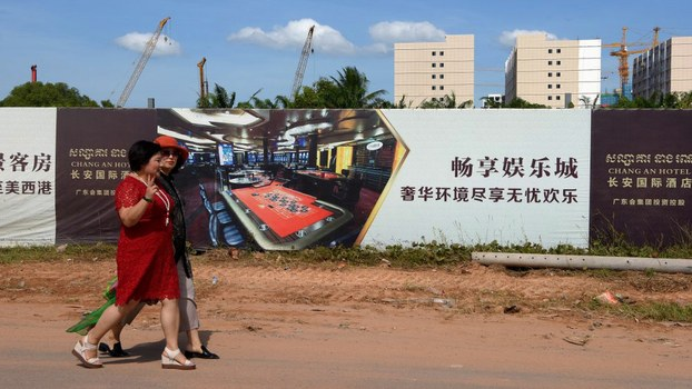 Chinese tourists walk along a construction site for a hotel and casino in Sihanoukville, the coastal capital of Preah Sihanouk province, Dec. 14, 2018.