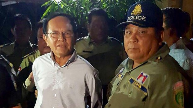 Cambodian opposition leader Kem Sokha (L) is escorted by police at his home in Phnom Penh, Sept. 3, 2017.