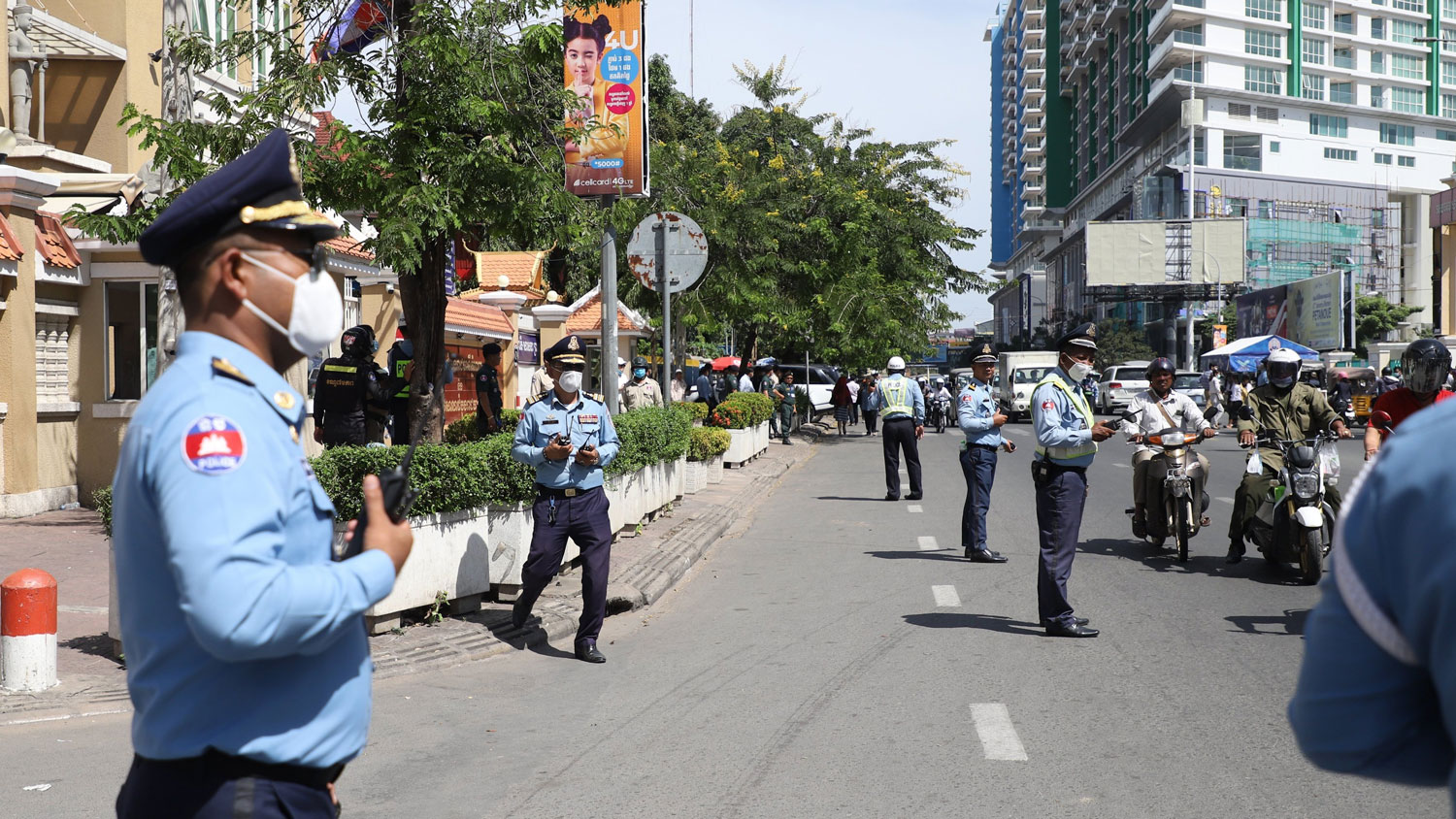 Police guard the streets in front of Cambodia's Phnom Penh Municipal Court, Nov. 26, 2020.