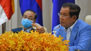 Cambodia's Prime Minister Hun Sen (R) speaks to the media beside Deputy Prime Minister and Minister of Council of Ministers Bin Chhin, wearing a face mask as a preventive measure against the coronavirus, during a press conference at the Peace Palace in Phnom Penh, April 7, 2020.