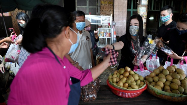 A vendor offers face masks, as a preventive measure against the novel coronavirus, to people at a market in Phnom Penh, March 17, 2020.