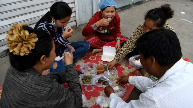 Cambodian workers sit down for lunch during a break in front of their factory in Phnom Penh, March 2, 2020.
