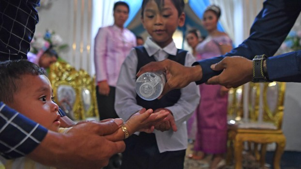 A child uses a hand sanitizer amid concerns over the spread of coronavirus, before attending a wedding party in Phnom Penh, March 21, 2020.