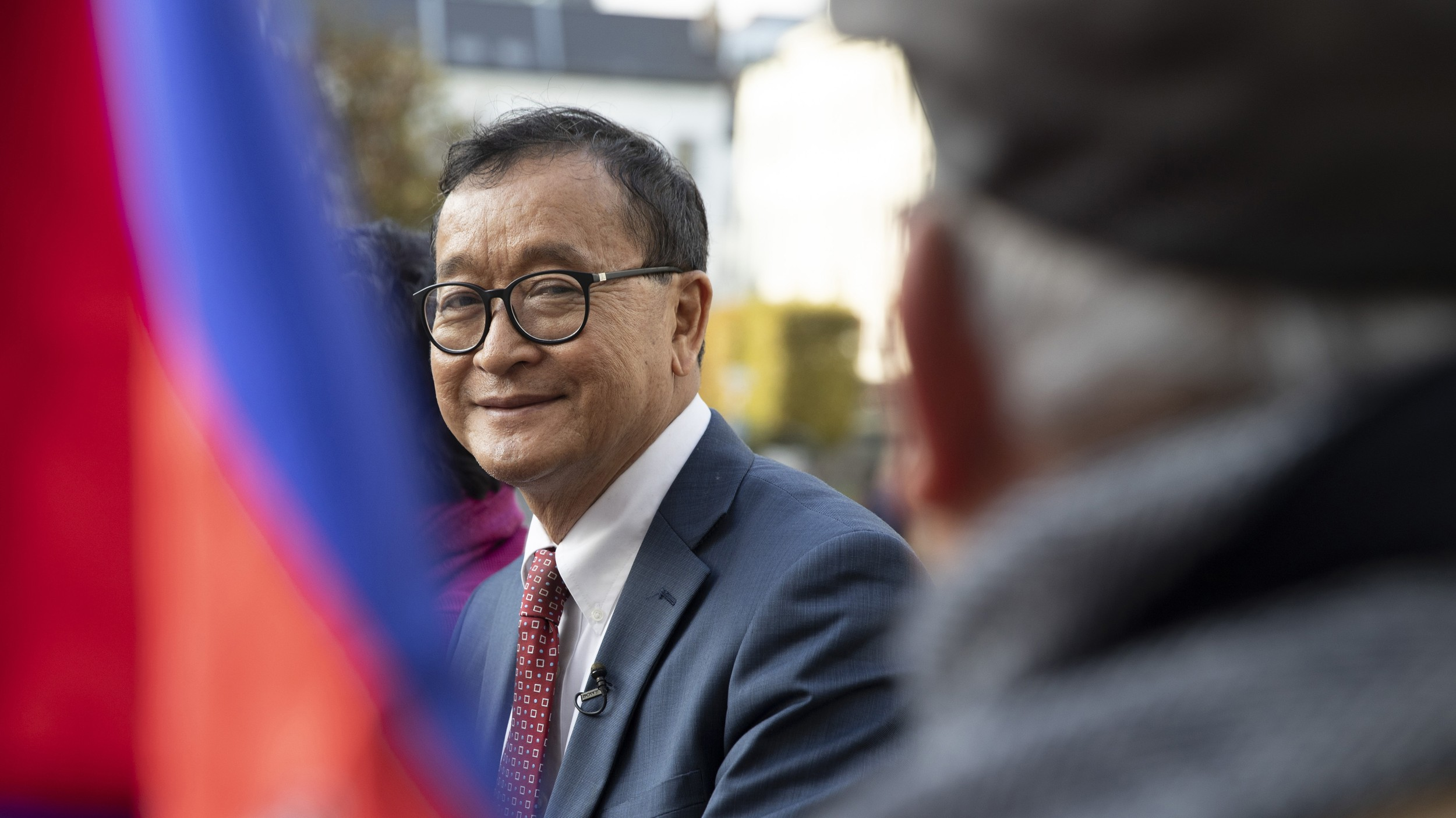 Cambodian opposition politician Sam Rainsy (C) speaks to a member of his delegation as he sits in front of the European Parliament in Brussels, Belgium, Nov. 4, 2019. Credit: AP Photo