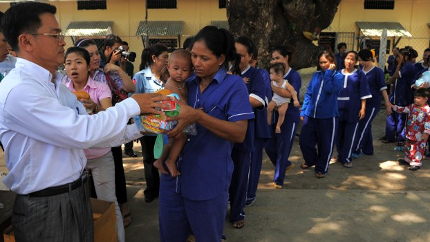 A representative of local rights group LICADHO offers food to a female inmate and her baby at Prey Sar prison in Phnom Penh, in a file photo.