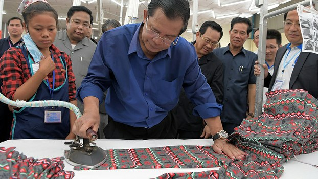 Cambodian Prime Minister Hun Sen (C) irons clothes at a garment factory on the outskirts of Phnom Penh, Aug. 30, 2017.