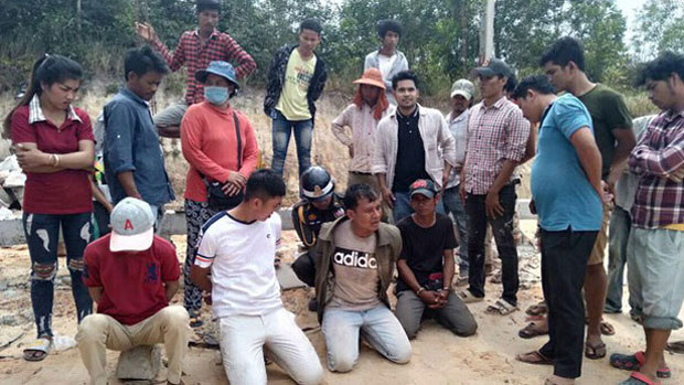 A police officer handcuffs villagers arrested after a land protest in Cambodia's Sihanoukville province, Jan. 24, 2019.