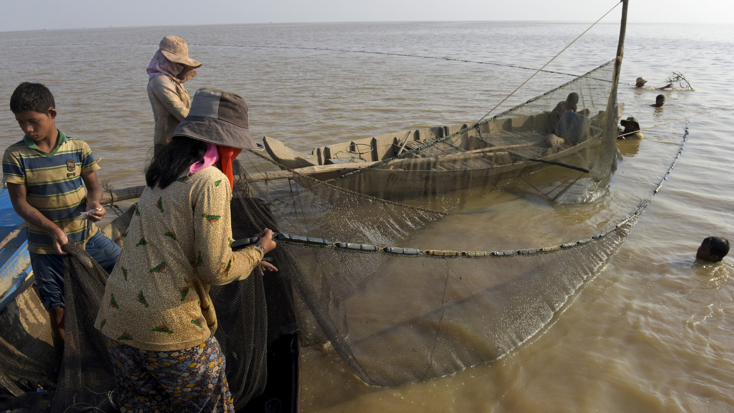 Villagers pull up a fishing net on the Tonle Sap Lake in Siem Reap, in a file photo.