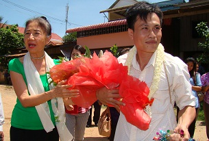 Leang Sokchouen (r) receives flowers from LICADHO President Pung Chhiv Kek (l) outside the Kandal provincial prison upon his release, May 30, 2012.