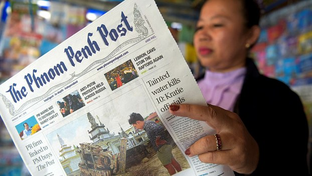 A Cambodian vendor reads the Phnom Penh Post newspaper at her newsstand in Phnom Penh, May 7, 2018.