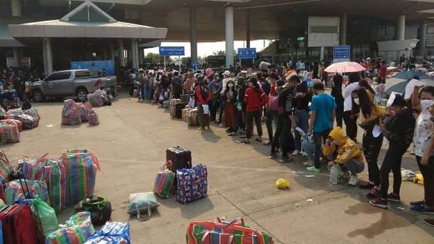 People line up at the immigration post by the second Thai-Lao Friendship Bridge in Mukdahan, as thousands of people attempted to cross from Thailand into Laos before the border crossing was set to close due to concerns over the spread of the COVID-19 coronavirus, March 23, 2020.