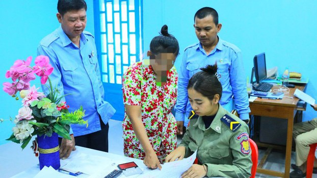 The mother of 'Tevy' thumbprints a document before being released from prison in Phnom Penh, Feb. 28, 2020.