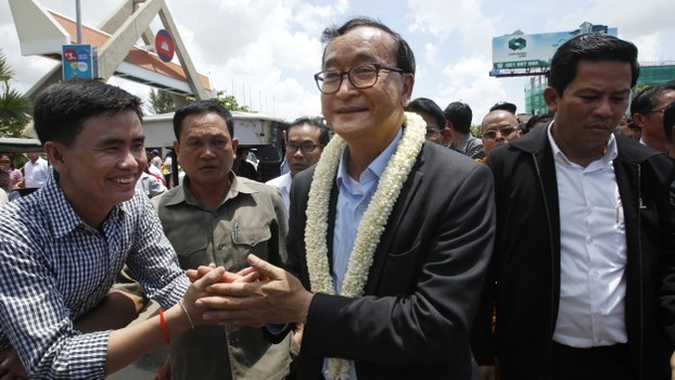 Sam Rainsy (C) greets party supporters upon his arrival at Phnom Penh International Airport in Phnom Penh, Cambodia, in a file photo taken shortly before he went into self-imposed exile.