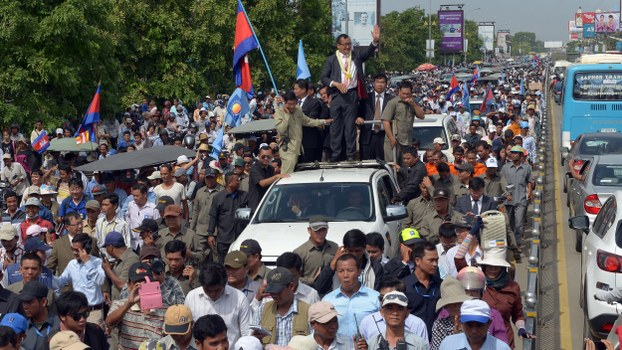 Cambodian opposition leader Sam Rainsy (top C) greets his supporters along a street in Phnom Penh, in a file photo.