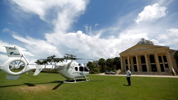 A man stands near a Union Development Group helicopter in front of an old casino at the Dara Sakor investment zone in Cambodia's Koh Kong province, May 6, 2018.