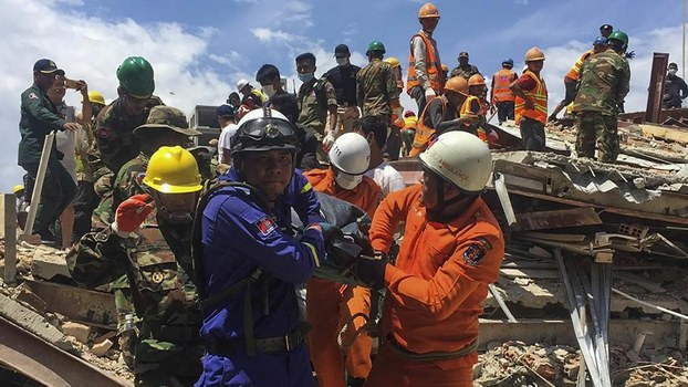 Rescue workers remove a victim from the debris after a Chinese-owned, seven-storey building collapsed in Cambodia's Sihanoukville, June 22, 2019.