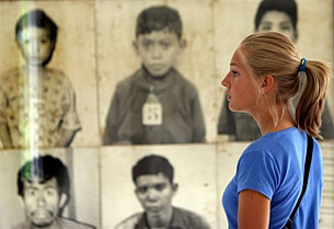 A tourist looks at photos of Khmer Rouge victims on display at Tuol Sleng Genocide Museum in Phnom Penh on Aug. 12, 2008. AFP/Tang Chhin Sothy