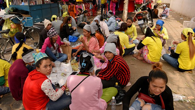 Cambodian workers sit down for lunch during break time in front of a factory in Phnom Penh, Feb. 12, 2019.