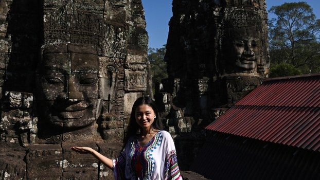 A Chinese tourist poses for photographs during a visit to the Angkor complex in Cambodia's Siem Reap province, Dec. 6, 2019.