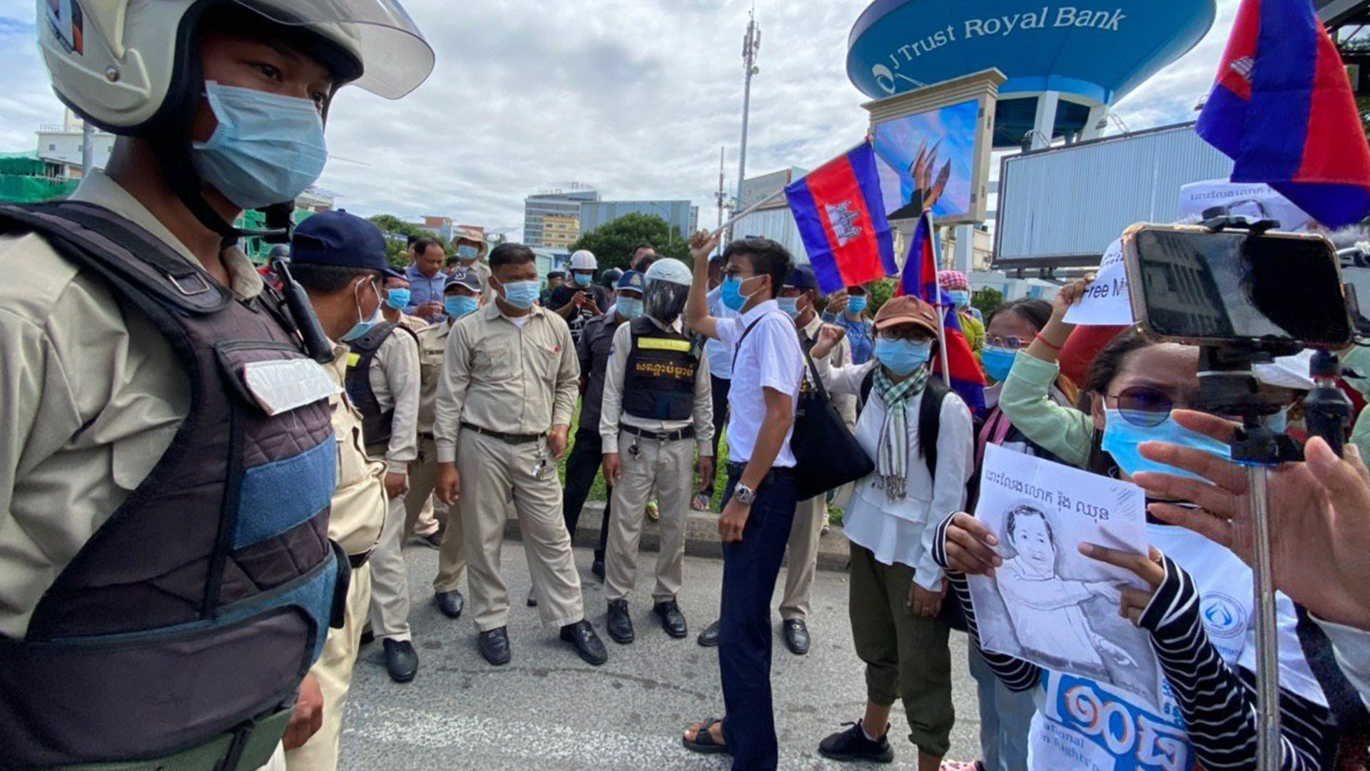 Protesters demanding the release of union leader Rong Chhun are monitored by security forces during a demonstration in front of the Phnom Penh Municipal Court in Phnom Penh, Aug. 5, 2020.