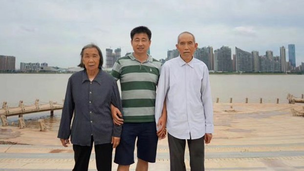 Hunan human rights lawyer Xie Yang, who was detained in China's July 9, 2015 crackdown on rights lawyers and subjected to abuse including torture and deprivation of food and water, poses with his parents in an undated photo.