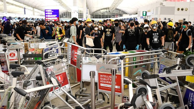 Pro-democracy protestors block the entrance to airport terminals after a scuffle with police at Hong Kong's international airport, Aug. 13, 2019.
