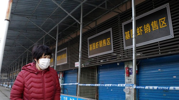 A woman walks in front of the closed Huanan wholesale seafood market in the city of Wuhan, in China's Hubei province, Jan. 12, 2020.