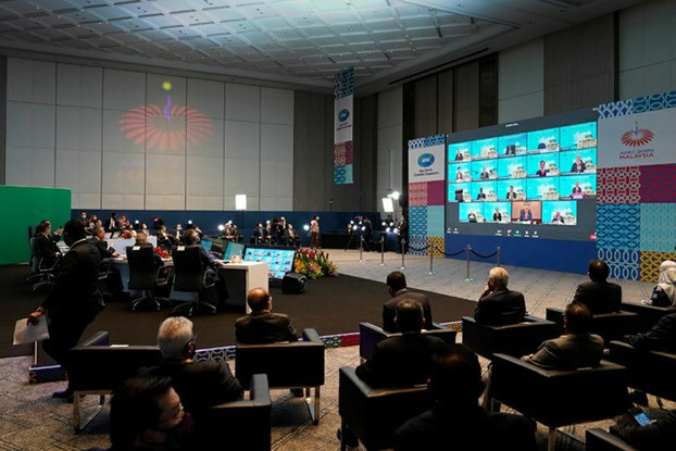 Officials from host nation Malaysia watch video monitors in Kuala Lumpur that show participants at the virtual Asia-Pacific Economic Cooperation forum, Nov. 20, 2020.
