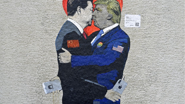 A mural depicting China's President Xi Jinping (L) holding an Apple iPhone kissing US President Donald Trump (R) holding a Huawei smartphone is displayed on a wall in Milan, Italy, June 29, 2019.